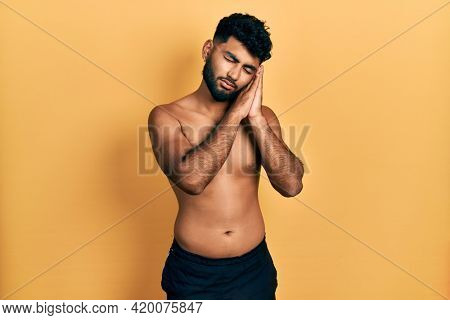 Arab man with beard wearing swimwear shirtless sleeping tired dreaming and posing with hands together while smiling with closed eyes.