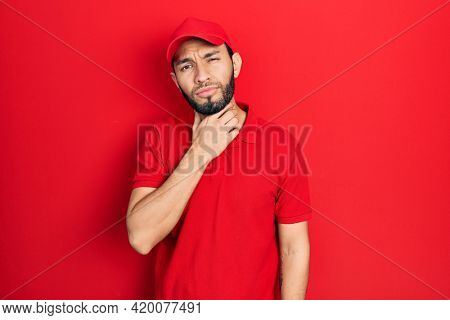 Hispanic man with beard wearing delivery uniform and cap touching painful neck, sore throat for flu, clod and infection