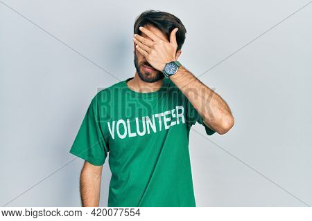 Young hispanic man wearing volunteer t shirt covering eyes with hand, looking serious and sad. sightless, hiding and rejection concept