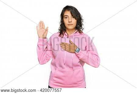 Young hispanic woman wearing casual sweatshirt swearing with hand on chest and open palm, making a loyalty promise oath