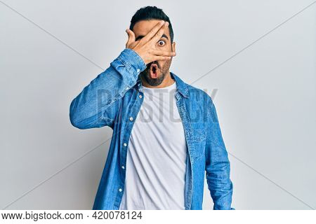 Young hispanic man wearing casual clothes peeking in shock covering face and eyes with hand, looking through fingers afraid