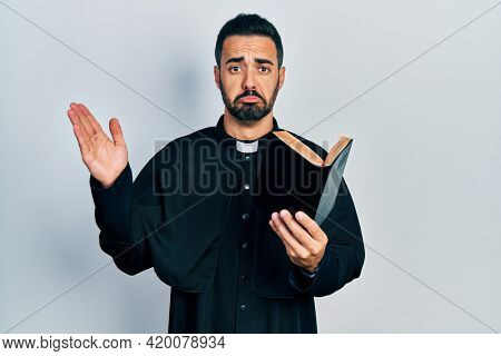 Handsome hispanic priest man with beard holding bible and christian cross depressed and worry for distress, crying angry and afraid. sad expression.