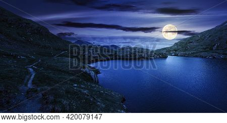 Summer Landscape With Lake On High Altitude At Night. Beautiful Scenery Of Fagaras Mountain Ridge In