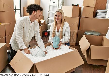 Young beautiful couple smiling happy unboxing cardboard box at new home.