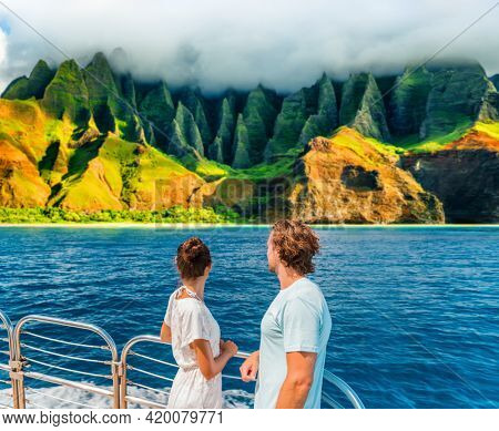 Hawaii Kauai Na Pali coast landscape scenic cruise. Couple watching dramatic mountains famous tourist destination on boat deck. Cruise ship on summer travel vacation and woman tourists relaxing.