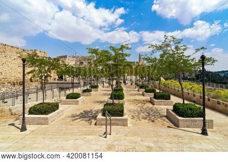 View of promenade with green trees and plants and ancient surrounding wall with Tower of David in old city of Jerusalem, Israel.