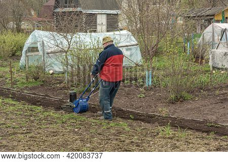 Poland, Lomza - May 01, 2021: A Farmer On A Private Farmstead Cultivates A Plot For Planting Plants.