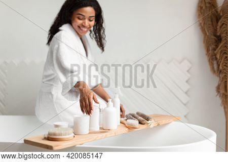 Black Woman In White Bathrobe Choosing Cosmetic Sitting In Bathroom