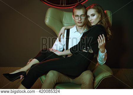 Handsome young man hugs his beloved woman, sitting on an armchair in a luxury apartment. Date. Glamorous lifestyle. Fashion shot.