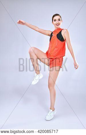 Sportswear fashion. Beautiful athletic girl model posing in modern sportswear on a light background at studio. Full length portrait.
