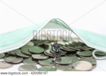 Business, Money, Covid-19 And Healthcare Concept. Businessman Miniature Figure People Sitting On Pil