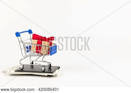 Metal Chrome Shiny Shopping Trolley On Wheels With Gift Box On Wallet With Dollars On White Backgrou