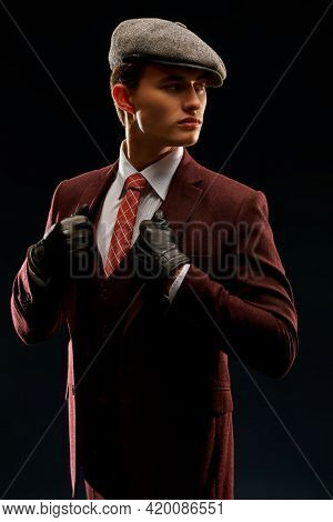 Men's beauty, fashion. Retro style. Handsome man in an expensive suit, a cap and leather gloves on a black background. Mafia man.