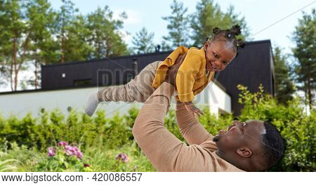family, fatherhood and mortgage concept - happy african american father playing with baby daughter over house and summer garden on background