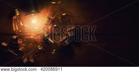 Stand Out In A Crowd. Leadership And Uniqueness Concept. Glowing Filament Light Bulb On Wooden Backg