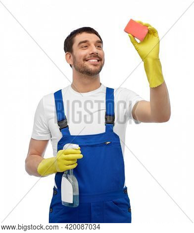 profession, cleaning service and people concept - happy smiling male worker or cleaner in overall and gloves with sponge and detergent over white background
