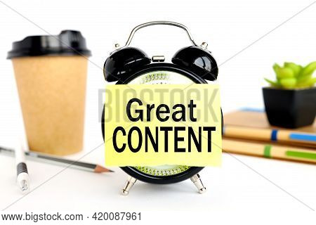 Great Content. There Is A Sticker On The Alarm Clock. Against The Background Of A Paper Cup With Cof