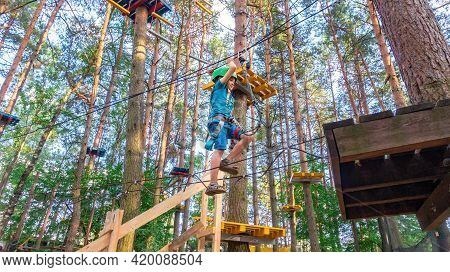 A Boy In A Helmet Climbs A Rope Ladder Stretched Between Trees In A High-rope Adventure Park. Family