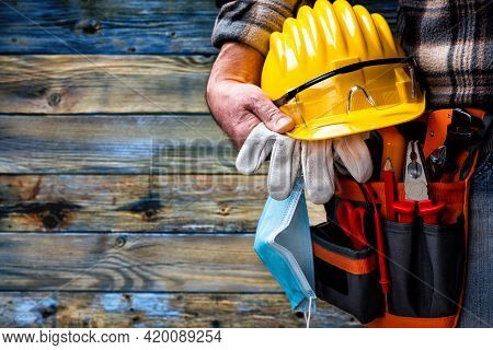 Electrician Worker On Vintage Light Blue Wooden Background; Holds Helmet, Gloves And Goggles In Hand