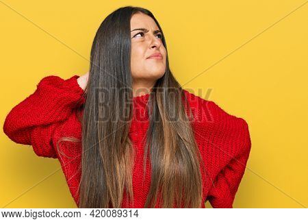 Beautiful hispanic woman wearing casual clothes suffering of neck ache injury, touching neck with hand, muscular pain