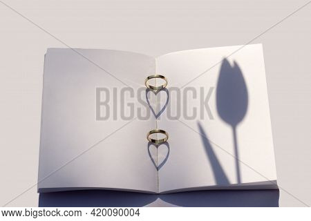 Spring Wedding Mockup. Blank Wedding Book On A White Table. Wedding Rings Are Placed On The Book And
