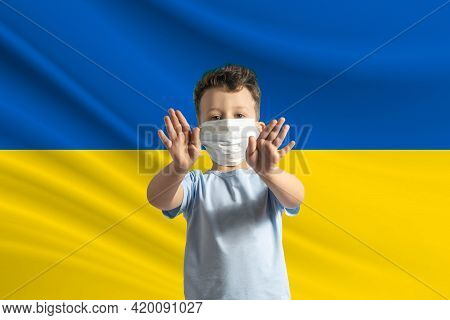 Little White Boy In A Protective Mask On The Background Of The Flag Of Ukraine. Makes A Stop Sign Wi