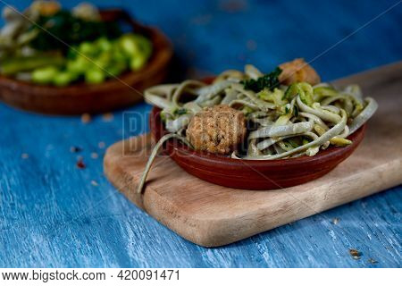 a dish with some spelt tagliatelle, kale and vegan meatballs, on a blue rustic wooden table, next to another dish with edamame beans, spelt tagliatelle, tofu, kale and shiitake mushrooms