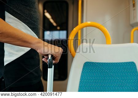 closeup of a young caucasian man, traveling as a passenger in a train or subway, standing and grabbing the telescopic handle of his suitcase