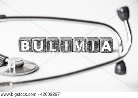 Stone Block Form Word Bulimia With Stethoscope. White Background. Medical Concept. Emotional Disorde