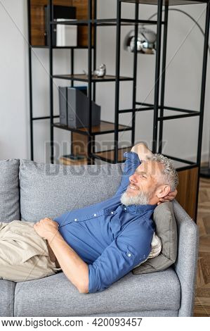 Vertical Portrait Of Calm And Tranquil Senior Bearded Guy Lying Down On The Comfortable Couch, Matur