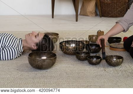Recovery With Alternative Medicine: Young Woman Practice Sound Therapy Of Singing Tibet Bowls Vibrat