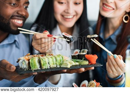 Lunch At A Asian Restaurant. Close Up Shot Of Happy Grinning Multiethnic Friends, Black Man And Two