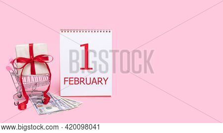 1st Day Of February. A Gift Box In A Shopping Trolley, Dollars And A Calendar With The Date Of 1 Feb