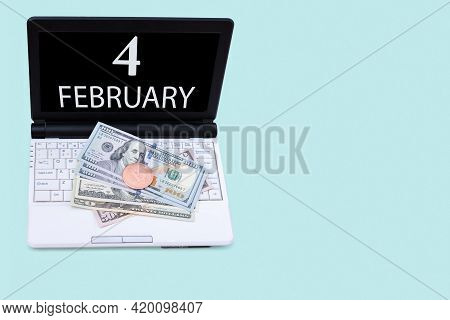 4th Day Of February. Laptop With The Date Of 4 February And Cryptocurrency Bitcoin, Dollars On A Blu