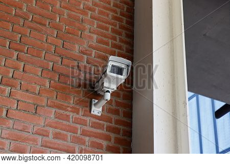 White Surveillance Camera Mounted On A Red Stone Wall, People Are Under Constant Surveillance In Tod