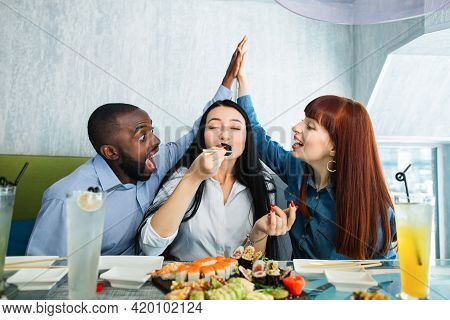 Tasty Food, The Pleasure Of Eating. Pretty Young Asian Woman Enjoying Tasty Sushi Roll, Sitting At T