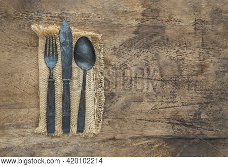 Rustic Ancient Vintage Cutlery In A Sackcloth On Rustic Wooden Table. Copy Space, Selective Focus.