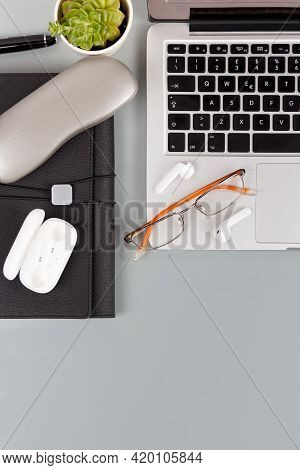 Laptop, Agenda, Glasses And Wireless Earphones On A Grey Background Top View With Copy Space