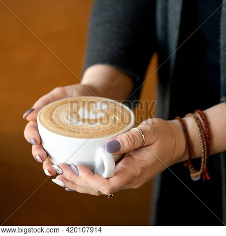 Cup Of Creamy Cappuccino Coffee In Female Hands. Woman Holds Portion Of Hot Aromatic Drink With Frot