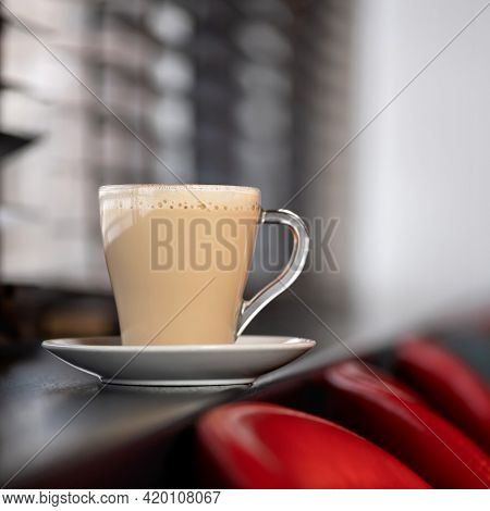 Glass Cup Of Latte Or Cappuccino Coffee With Froth On Blurred Background. Aromatic Hot Drink On Wind