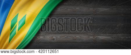 Saint Vincent And The Grenadines Flag On Black Wood Wall. Horizontal Panoramic Banner. 3d Illustrati