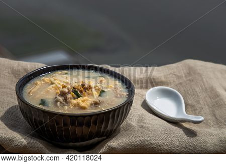 Pork Congee Or Chinese Rice Porridge With Minced Pork, Egg, Enoki Mushroom And Seaweed In Bowl With