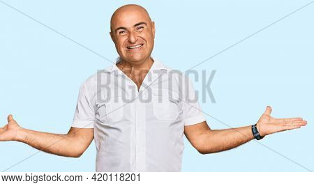 Mature middle east man with mustache wearing casual white shirt smiling showing both hands open palms, presenting and advertising comparison and balance