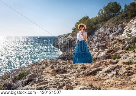 A Girl In A Hat Stands On The Seashore. The Woman Is Looking At The Sea. Travel To The Sea. Rocky Se