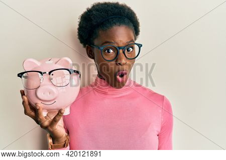 Young african american girl holding piggy bank with glasses scared and amazed with open mouth for surprise, disbelief face