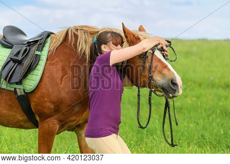 Caucasian Woman Is Putting A Black Bridle On Her Horse In Outdoors.