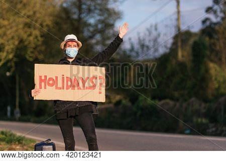 Young Girl In Hat And Anti Virus Mask Doing Auto Stop On The Road With A Sign Asking About Holidays.