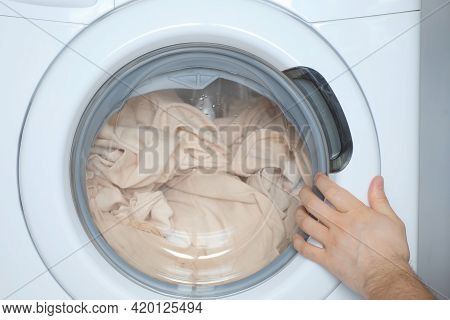 Mans Hands Loading The Washing Machine With Beige Bed Linen, Laundry At Home. Man Is Doing His Laund