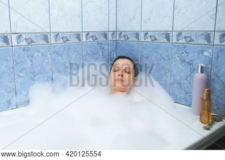Young Woman With Closed Eyes Is Relaxing Lying In Bath With Foam At Home After Busy Day. Spa Treatme