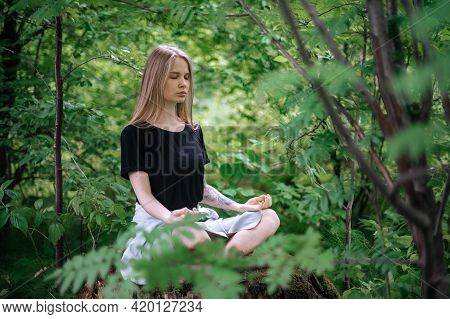 Practice Of Meditation And Interaction With Nature. Girl In Green Forest